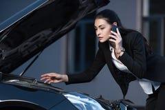 Ung attraktiv affärskvinna som ser under huven av passagerarebilen och samtal Royaltyfria Bilder