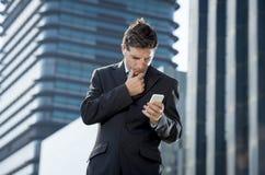 Ung attraktiv affärsman i dräkt och slips som utomhus ser textmeddelandet på mobiltelefonen Royaltyfria Foton