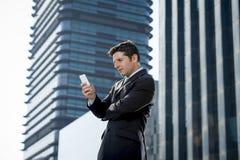Ung attraktiv affärsman i dräkt och slips som utomhus ser textmeddelandet på mobiltelefonen Arkivfoton