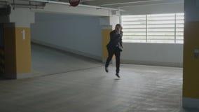 Ung attraktiv affärsman som bär formell dräktbanhoppning och rolig dans i en underjordisk parkeringsplats på hans väg till det bi arkivfilmer