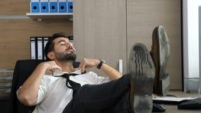Ung attraktiv affärsman som har en videokonferens via hans telefon arkivfilmer