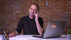 Ung attraktiv affärsman som talar över telefonen, medan sitta i kontoret med tegelstenväggen bakom arkivfilmer