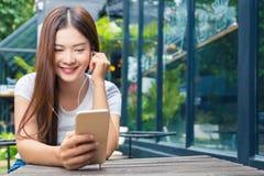Ung attraktiv asiatisk kvinna i tillfällig kläder som sitter utomhus- l Arkivbilder