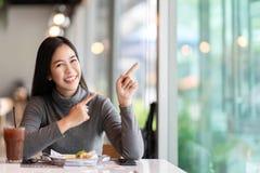 Ung attraktiv asiatisk kvinna som upp till pekar sidan för uppvisning av meddelandet som känner lyckligt häpet på kafét royaltyfri bild