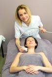 Ung attraktiv blond kosmetologkvinna som gör en ansikts- massage t Arkivbilder