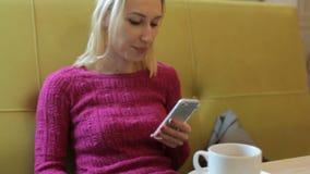 Ung attraktiv blond kvinna som använder app på mobiltelefonen i kafét som dricker kaffe lager videofilmer