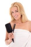Ung attraktiv blondin med hårborstar på vit bakgrund Royaltyfria Bilder