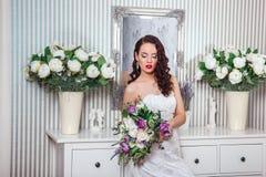 Ung attraktiv brud med blommor inomhus Morgon för brud` s Väntande brudgum för lycklig brud Royaltyfri Fotografi