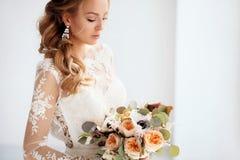 Ung attraktiv brud med en bröllopbukett fotografering för bildbyråer