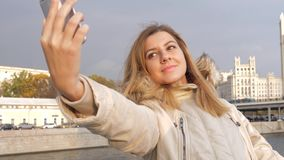 Ung attraktiv brunettkvinna i varma Autumn Jacket Making Selfie stock video