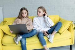 Ung attraktiv dam f?r aff?r tv? i tillf?llig kl?der som tillsammans sitter p? den gula soffan royaltyfria foton