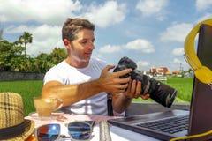 Ung attraktiv digital nomadman eller fotograf som utomhus arbetar på linje med den bärbar datordatoren och mobiltelefonen som den arkivbild