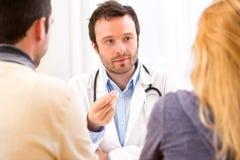 Ung attraktiv doktor som råder ett ungt par av patienter Arkivbilder