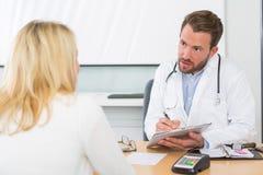 Ung attraktiv doktor som tar anmärkningar, medan patienten talar Arkivbilder