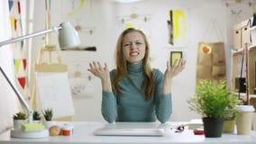 Ung attraktiv förvirrad kvinna vid tabellen lager videofilmer