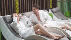 Ung attraktiv familj som vilar på soldagdrivarna i Spa stock video
