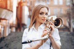 Ung attraktiv flicka i den vita skjortan med ett saxofonanseende i den utomhus- gatan - Sexig ung kvinna med saxofonen som ser ka Royaltyfri Fotografi