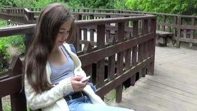 Ung attraktiv flicka som använder mobiltelefonen på bänk oklarheter över vita parksommartrees leende Panorama för kamera för HD-s lager videofilmer