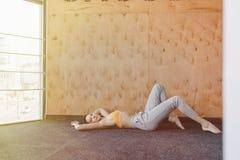 Ung attraktiv flicka som g?r kondition?vningar med yoga p? golvet p? en tr?bakgrund royaltyfria bilder