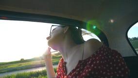 Ung attraktiv flicka som lutar ut ur fönstertappningbilen och tycker om ritt i sommartid Sol som skiner på bakgrund arkivfilmer