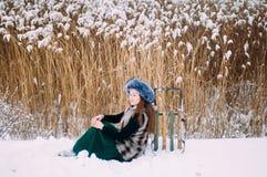 Ung attraktiv flicka som omfamnar den insnöade vintern Vinterportr royaltyfri bild