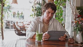 Ung attraktiv gladlynt man som använder modern digital grön fruktsaft för minnestavla och för drink på den nya vinden som ler man lager videofilmer