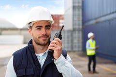 Ung attraktiv hamnarbetare som använder talkiewalkie på arbete Fotografering för Bildbyråer