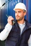 Ung attraktiv hamnarbetare som använder talkiewalkie på arbete Royaltyfria Foton
