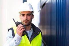 Ung attraktiv hamnarbetare som använder talkiewalkie på arbete Arkivfoton