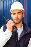 Ung attraktiv hamnarbetare som använder talkiewalkie på arbete Royaltyfri Fotografi