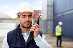 Ung attraktiv hamnarbetare som använder talkiewalkie på arbete Arkivfoto