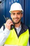 Ung attraktiv hamnarbetare som använder talkiewalkie på arbete Royaltyfria Bilder