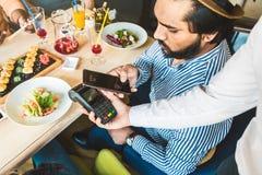 Ung attraktiv hinduisk man som betalar i kaf? med contactless smartphonebetalning royaltyfria bilder