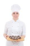Ung attraktiv kockkvinna i likformig med muffin som isoleras på Arkivfoton