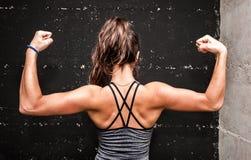 Ung attraktiv konditionflicka som tillbaka visar hennes muskler efter hård genomkörare i idrottshallen arkivfoton