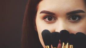 Ung attraktiv kvinna för makeupkonstnär som rymmer borstar och arrangerar i en studio på en svart bakgrund Under denna tid honom stock video