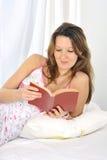 Ung attraktiv kvinna, i att ligga för nattlinne som kopplas av på den läs- nya boken för säng Arkivbilder