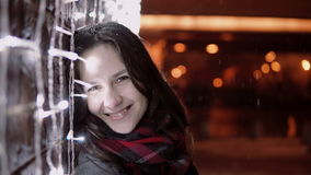 Ung attraktiv kvinna i den fallande snön på julnatten som ser kameran som står den near ljusväggen, stock video