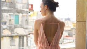 Ung attraktiv kvinna i klänning på gammal balkong i lägenhet i havannacigarr stock video