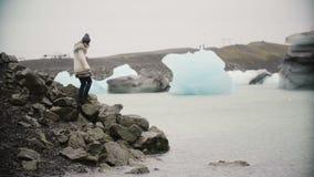 Ung attraktiv kvinna i lopapeysaanseende i islagun Turist som undersöker den berömda sikten av Island bara arkivfilmer