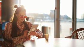 Ung attraktiv kvinna i röd solglasögon med minnestavladatorsammanträde i kafé Härlig flicka, i flygplats eller shoppping arkivfilmer