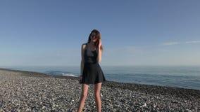 Ung attraktiv kvinna i solglasögon på Pebblet Beach stock video