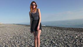 Ung attraktiv kvinna i solglasögon på Pebblet Beach arkivfilmer