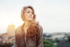 Ung attraktiv kvinna med bra lynne som tycker om härligt stadslandskap, medan stå på ett tak av byggnad som charmar le höften royaltyfria foton