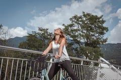 Ung attraktiv kvinna med cykeln på en bro arkivfoto