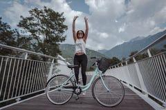 Ung attraktiv kvinna med cykeln p? en bro fotografering för bildbyråer