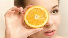 Ung attraktiv kvinna med en skiva av apelsinen Royaltyfri Foto