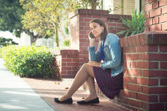 Ung attraktiv kvinna med telefonen på den soliga gatan Fotografering för Bildbyråer