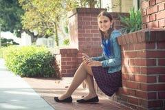 Ung attraktiv kvinna med telefonen på den soliga gatan Arkivbild