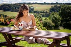 Ung attraktiv kvinna och att läsa en utomhus- bok och att tycka om kaffe Arkivfoto